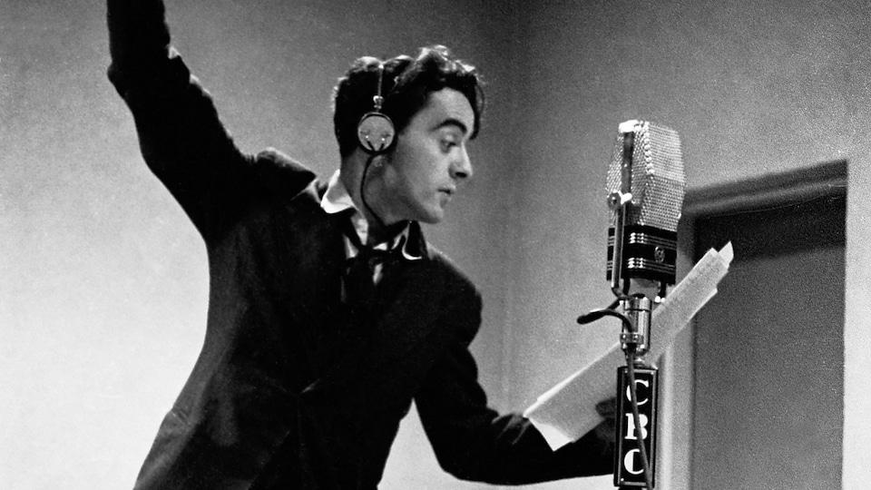 Dans un studio de radio, derrière un microphone sur pied, Guy Mauffette s'exprime, les bras en l'air.