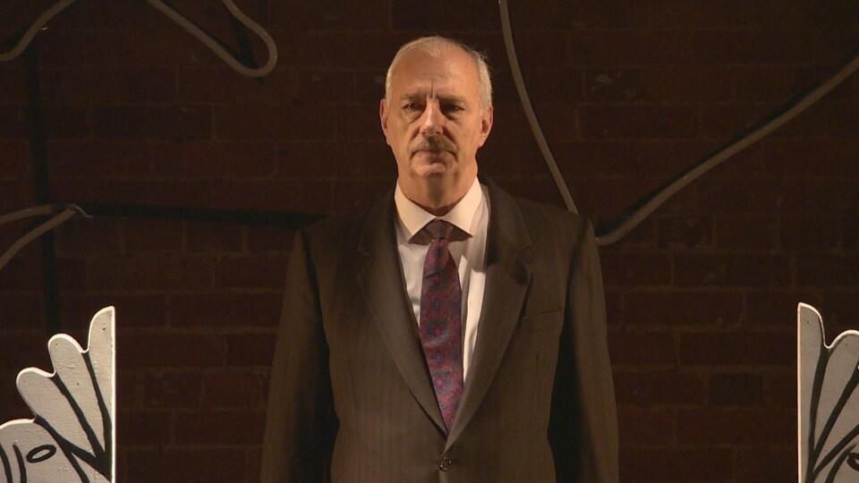 Guy Mignault en train de faire une tirade alors qu'il joue le rôle de Géronte dans le menteur de Corneille, il porte un veston noir, a les traits tirés et sérieux et une cravate violette