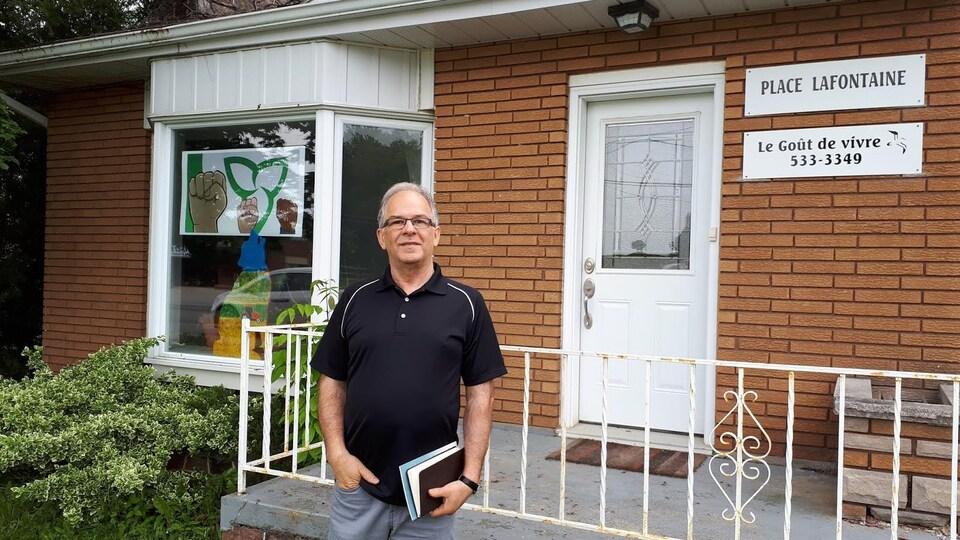 Un homme devant une maison avec une pancarte le goût de vivre.