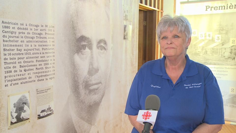 Guylaine Rioux est à côté d'une pancarte avec le visage de McCormick en gros plan qui raconte l'histoire de McCormick.