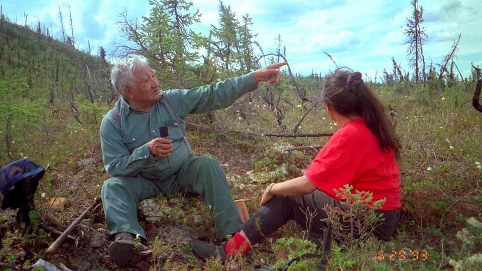 Deux personnes sont assises dans un champ.