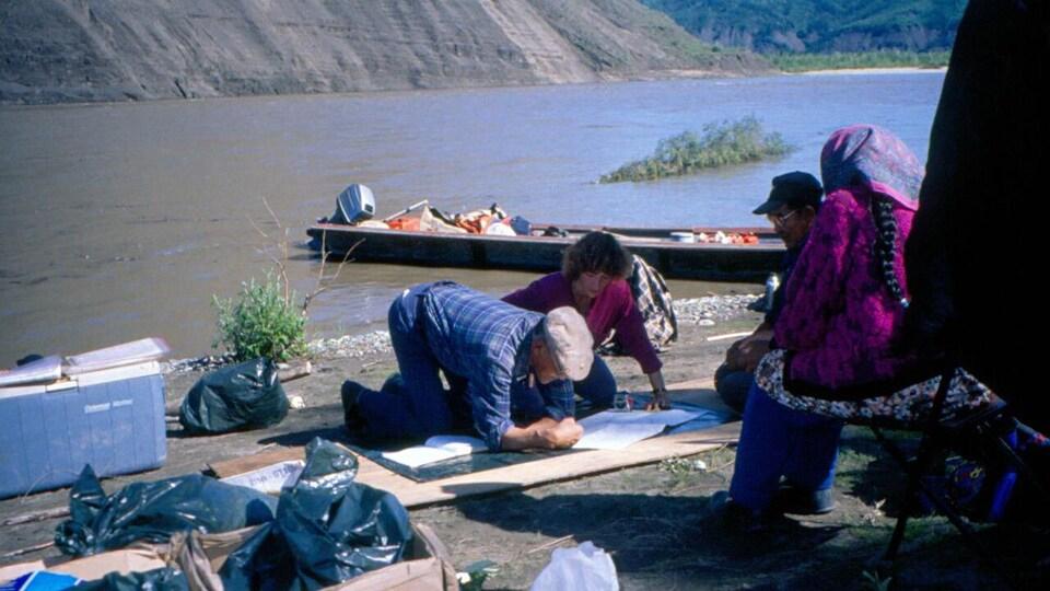 Un groupe de personnes est penché sur une carte près d'un lac.