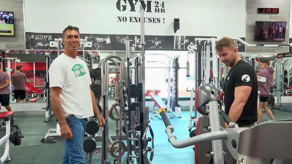 Le propriétaire d'une salle d'entraînement discute avec un client.