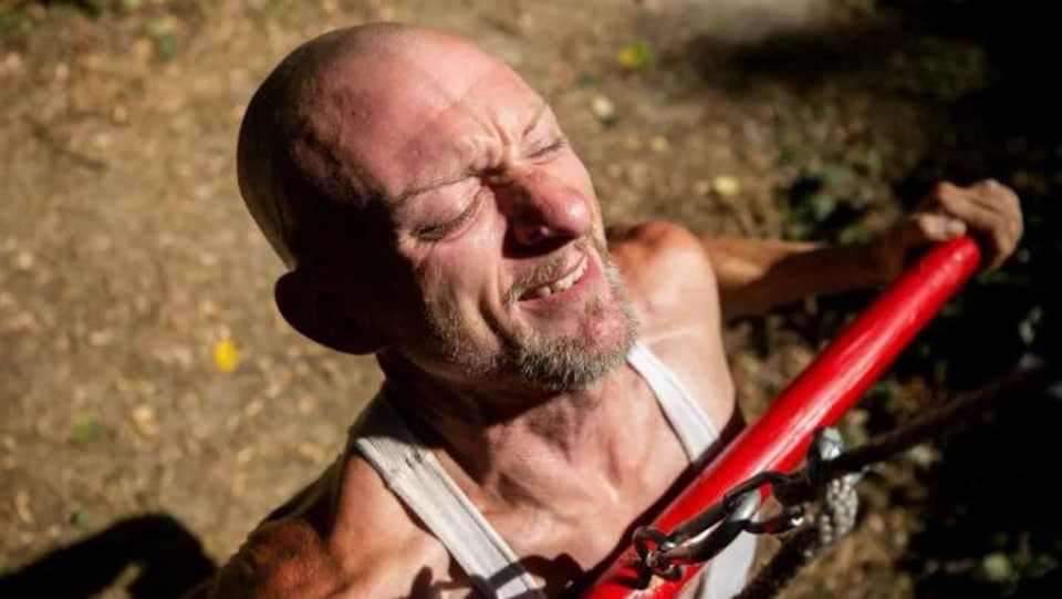 Un homme, les yeux fermés, tente de tirer sur une barre de métal attachée à une chaîne.