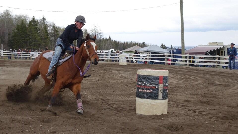 Une cavalière fait tourner son cheval baie près d'un baril.