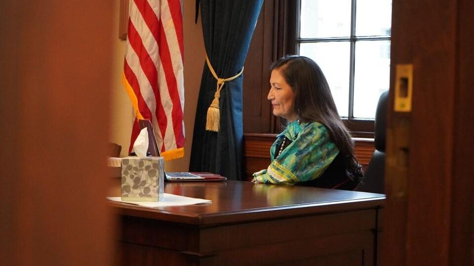 Une femme assise de profil dans un bureau.