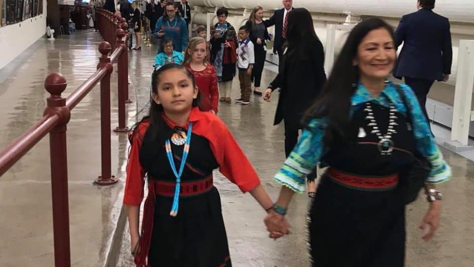 Une femme et une fille marchent main dans la main.
