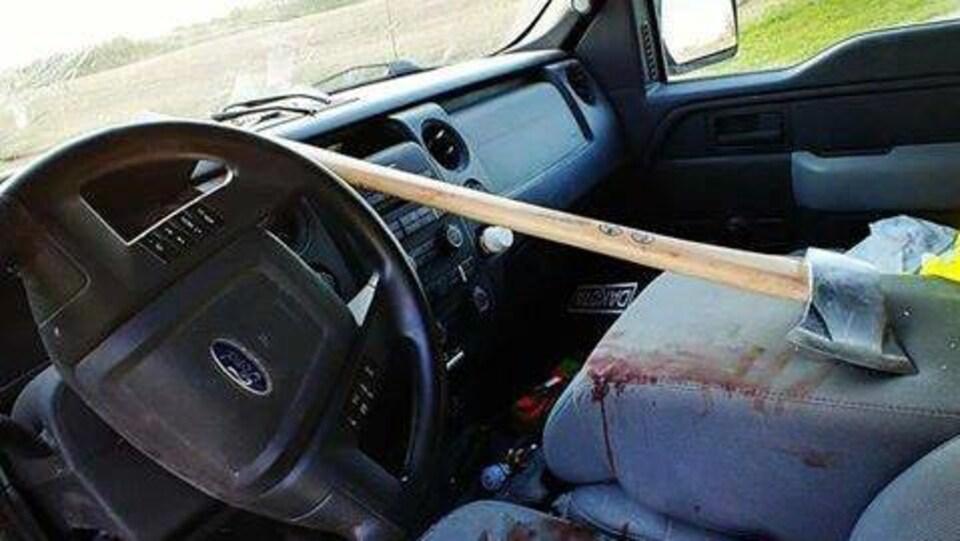 Photo de l'intérieur d'une voiture prise depuis la porte du conducteur. Une grande hache repose sur le siège du conducteur. Les sièges sont ensanglantés, avec des débris de verre venant  du parebrise, qui est lui-même détruit.