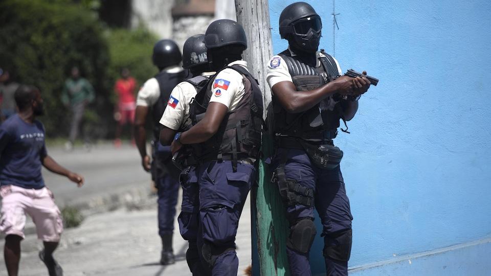 Des policiers se tiennent prêts, leurs armes dégaînées.