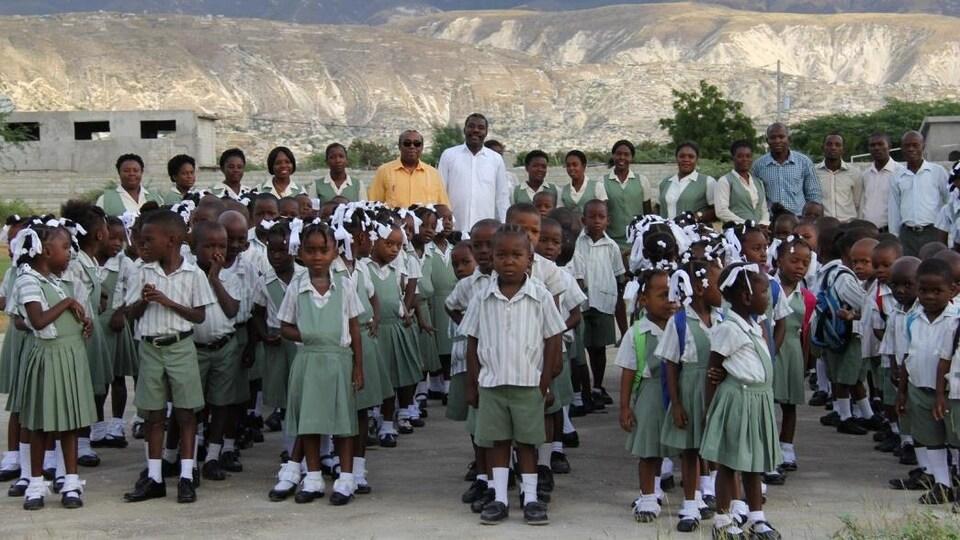 Des élèves de l'école élémentaire Saint-Paul, en rang sur le site de l'établissement en construction, accompagnés de M. Antoine Dérose et du corps enseignant. En arrière plan, les montagnes déboisés d'Haïti.