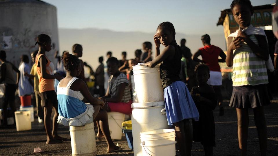 Des enfants haïtiens de Cité Soleil près de Port-au-Prince attendent la distribution d'eau potable.