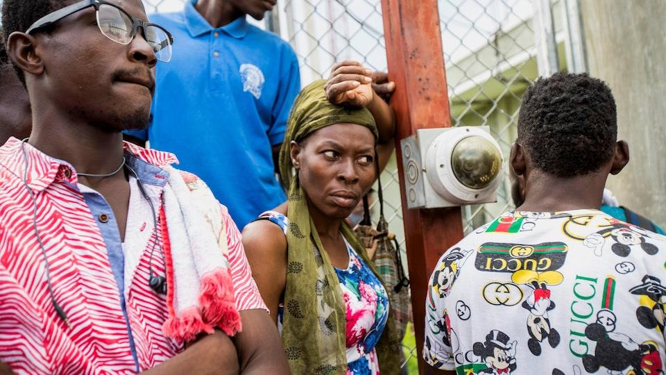 Trois hommes et une femme attendent derrière un grillage.