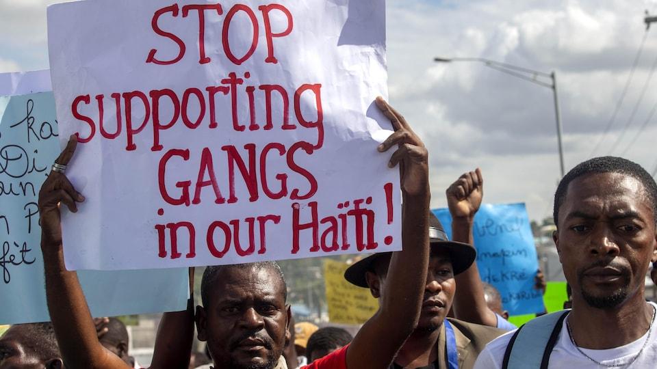 Un homme brandit une affiche dans une foule de manifestants.