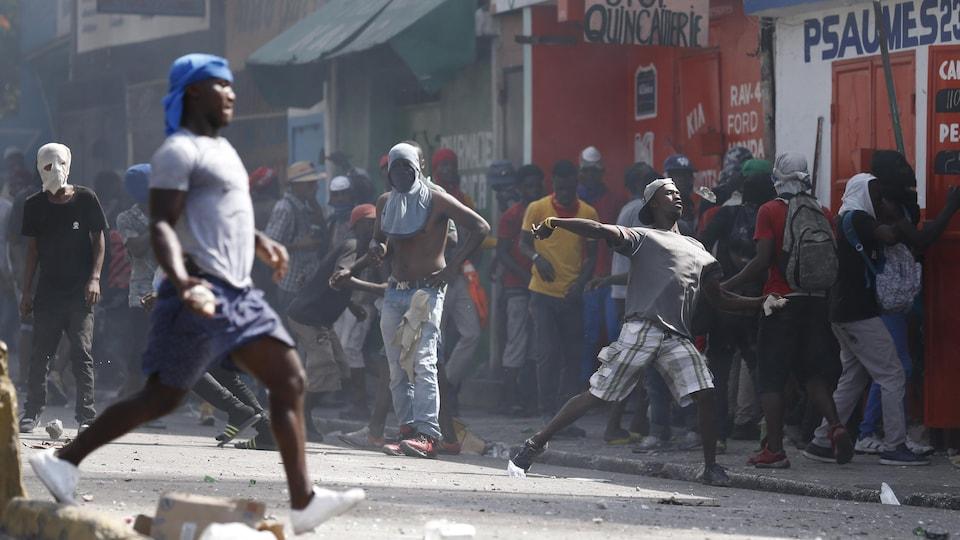 Des citoyens lancent des pierres lors d'une manifestation contre le gouvernement à Port-au-Prince.