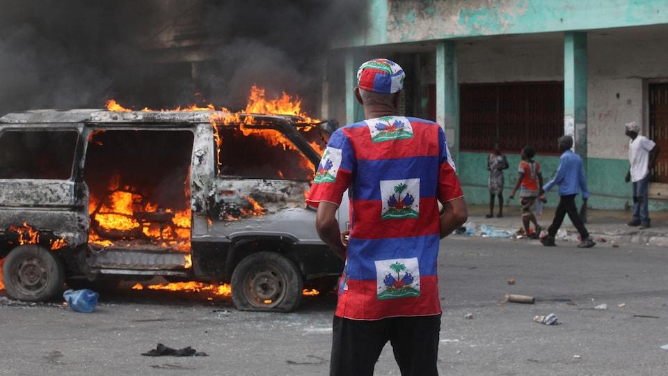 Un homme vêtu d'une tunique aux couleurs nationales se tient devant une fourgonnette en flammes dans une rue haïtienne.