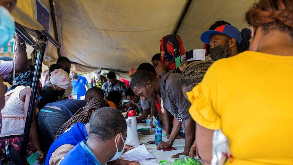 Une foule de gens s'enregistrent auprès des autorités locales, sous une tente.