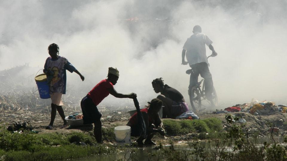 Des Haïtiennes lavent leur linge dans un ruisseau, alors que des ordures brûlent dans une décharge à L'Estère, le 18 janvier 2008