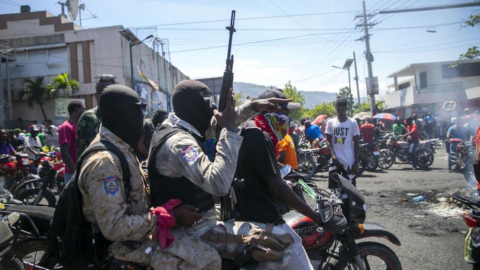 Des policiers armés et masqués roulent sur une même moto lors d'une manifestation dans les rues de Port-au-Prince.