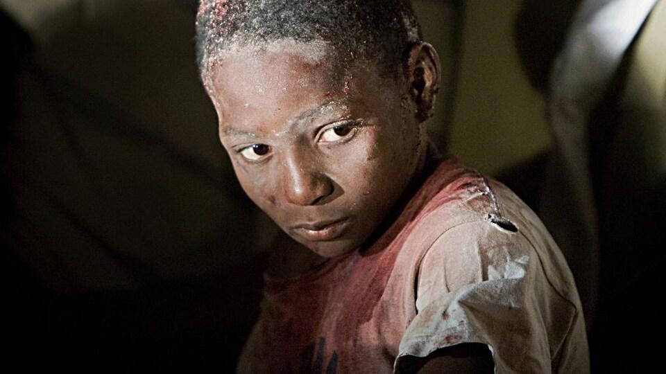 Gros blanc d'un garçon dont le chandail blanc est maculé de sang.