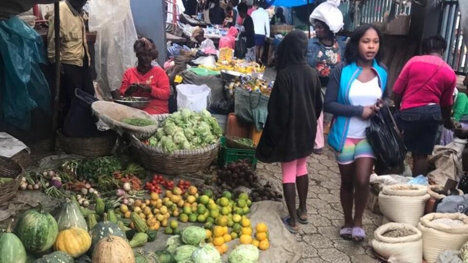 Une femme assise avec des produits frais devant elle.