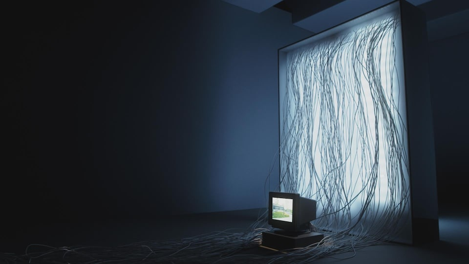 Une photo montrant un vieil ordinateur posé à l'horizontale surmonté d'un écran cathodique. L'appareil se trouve sur le sol, devant une installation lumineuse de laquelle sortent des dizaines de câbles informatiques qui pendent jusqu'au sol.