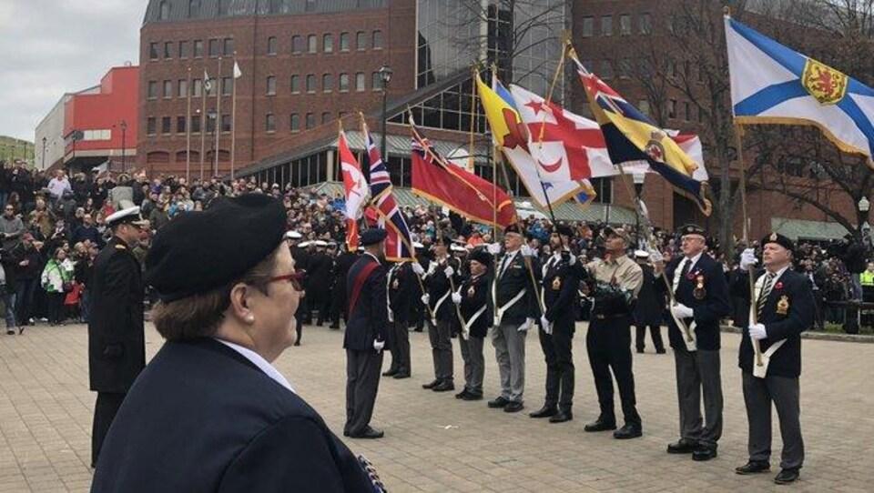 Des militaires portent des drapeaux devant la foule.