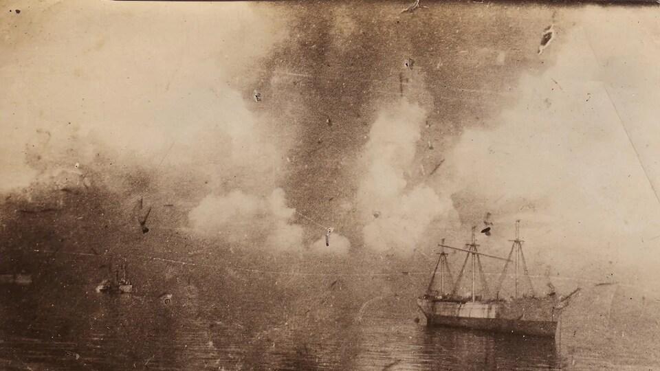 Ancienne photographie montrant des navires sur lesquels tombent des débris devant un gigantesque panache de fumée.