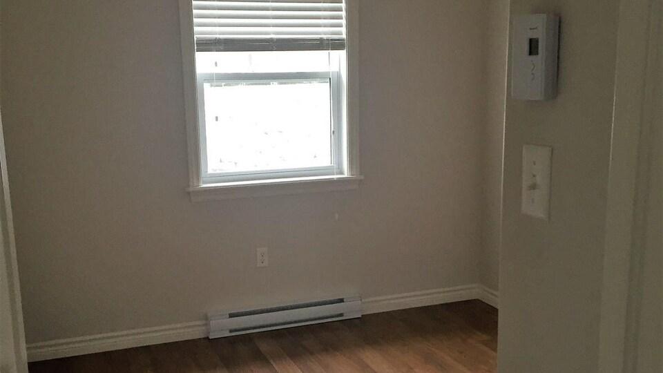 Une petite plinthe électrique sous une fenêtre dans une chambre