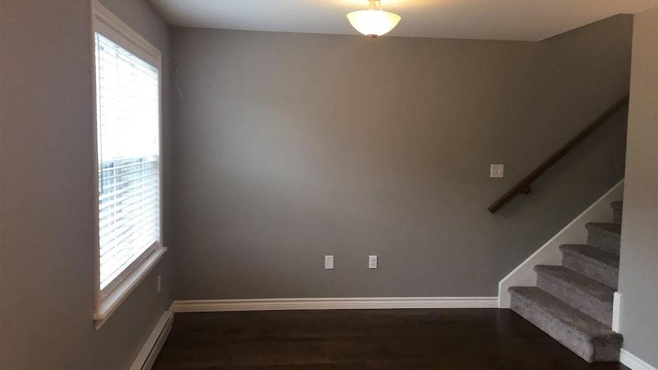 Une pièce au rez-de-chaussée avec une grande fenêtre et l'escalier menant à l'étage