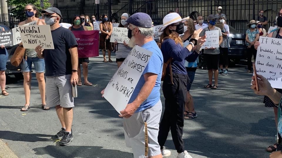 Des gens manifestent devant l'édifice de l'Assemblée législative.