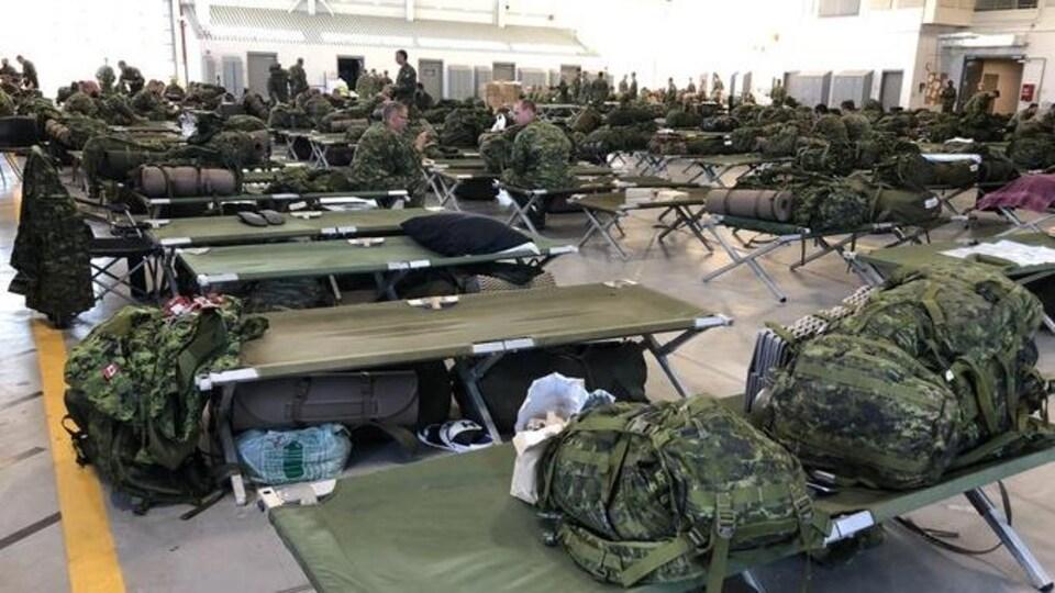 Des soldats installent des lits de camp dans une grande salle.