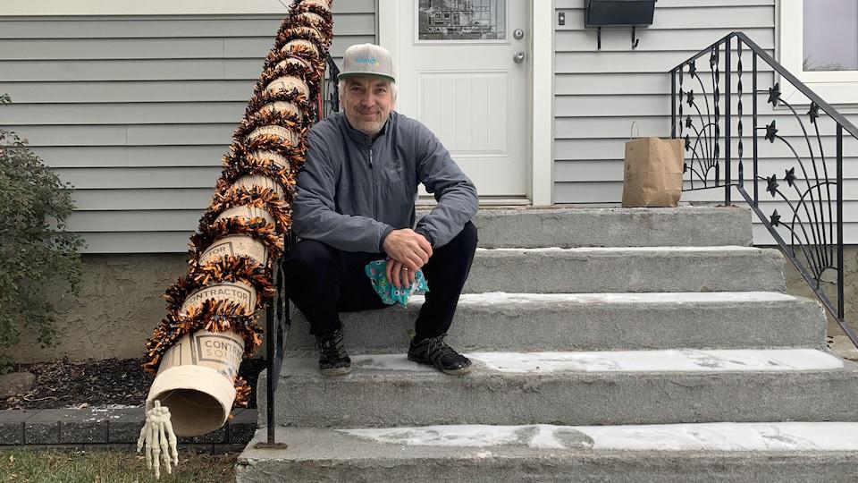 Glenn Kubish assit à côté de sa chute à bonbons devant chez lui.
