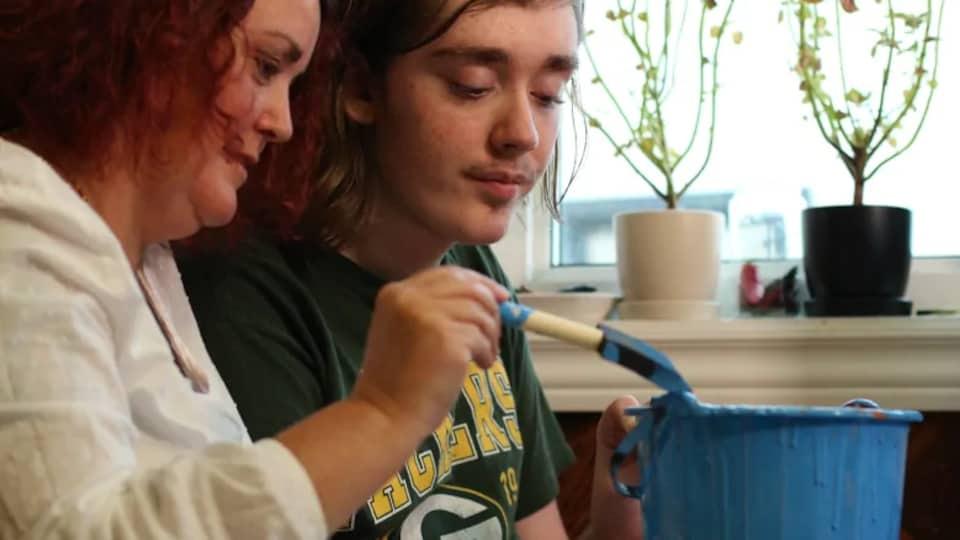 Une mère et son garçon peignent une citrouille en bleu.