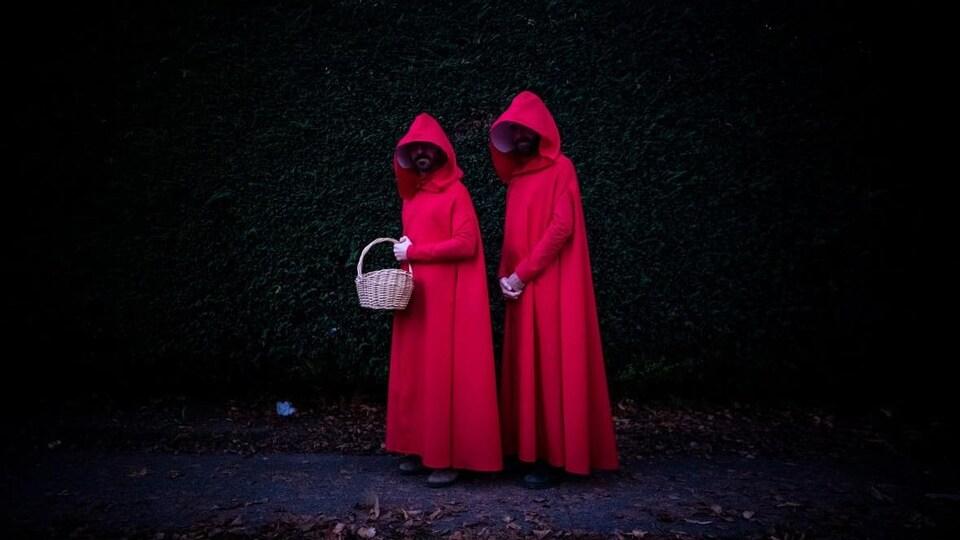 Deux hommes vêtus d'une longue cape rouge le soir de l'Halloween.
