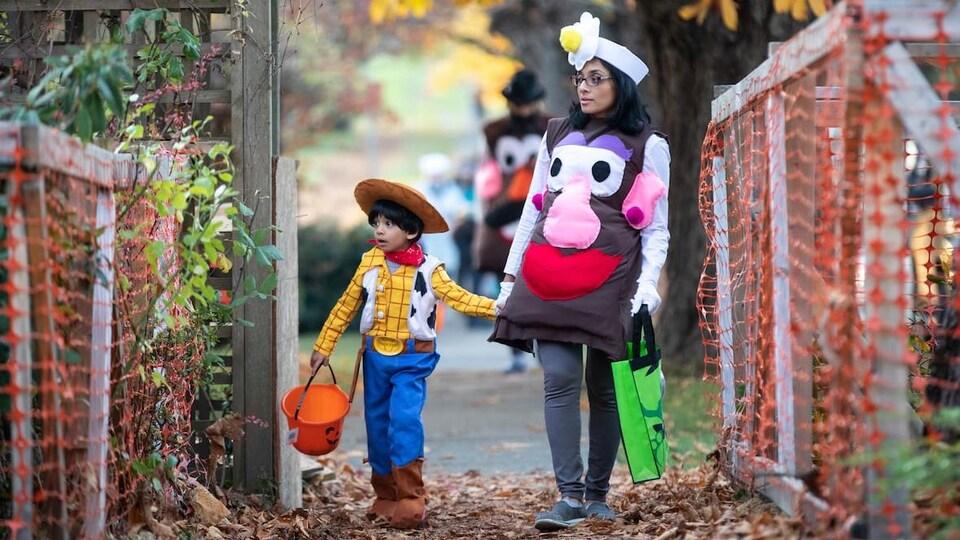 Une femme et un enfant costumés marchent main dans la main à l'Halloween.