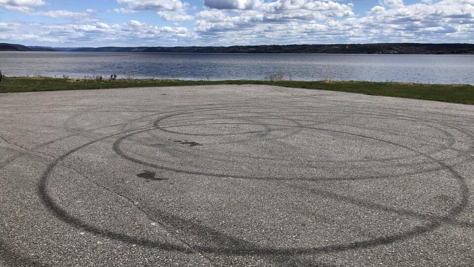 Des traces de pneus en rond sur l'asphalte.