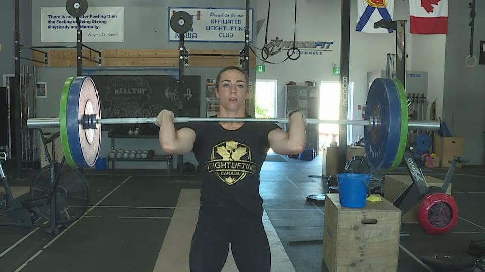 Une jeune femme soulève des haltères très lourds.