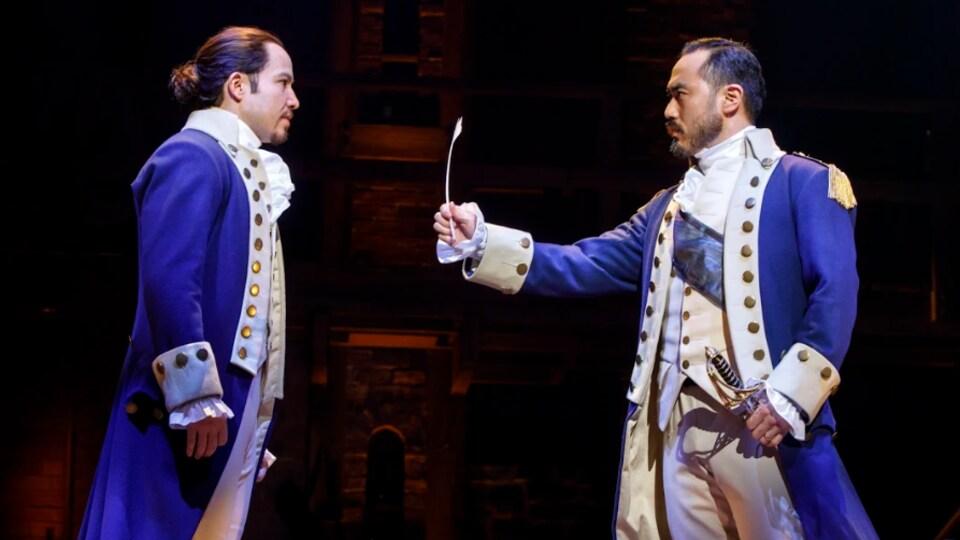 Deux comédiens incarnant les personnages d'Alexander Hamilton et Georges Washington sur scène.