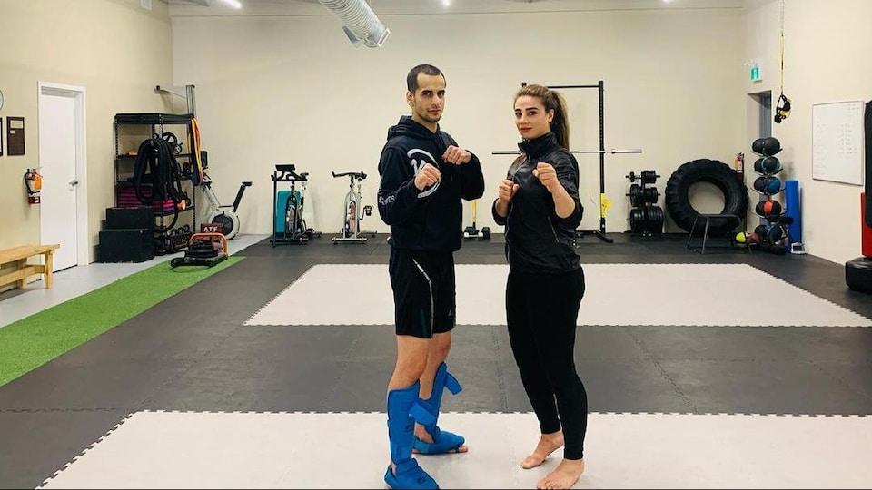 Ils posent dans une salle d'entraînement les deux poings en l'air.