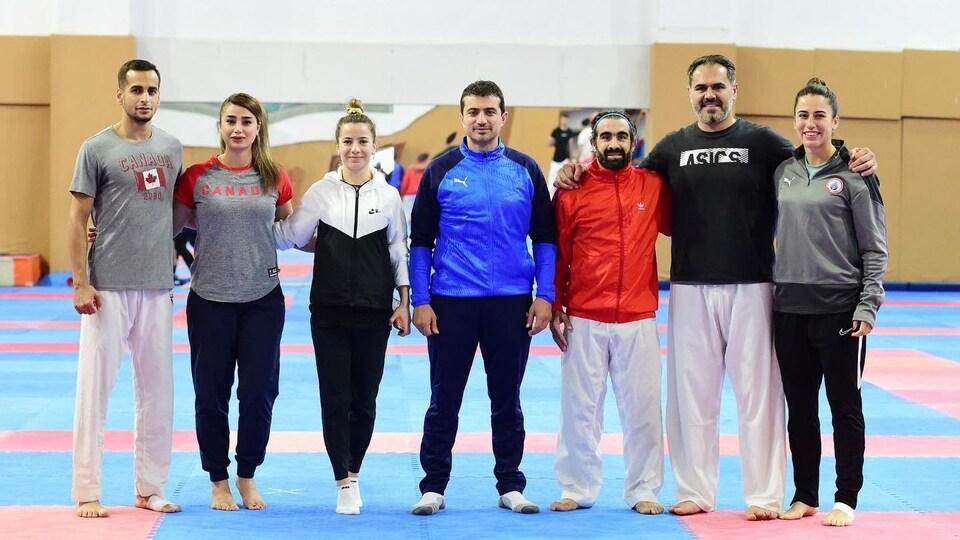 Hamoon Derafshipour et sa femme Samira Malekipour portent un chandail sur lequel il est inscrit Canada. Ils se tiennent aux côtés d'autres athlètes dans une salle d'entraînement.