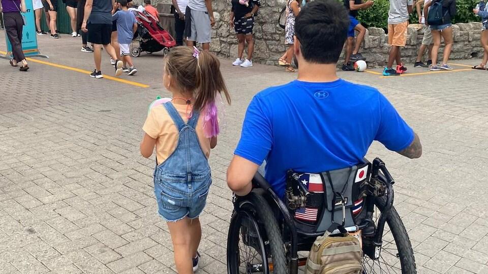 Ahmad El Nasser dans un fauteuil roulant de dos et à côté de sa nièce.