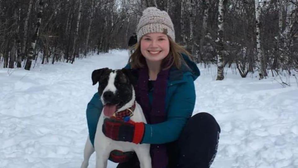 Une jeune femme et son chien dans un paysage hivernal.
