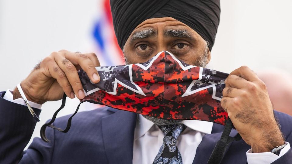 M. Sajjan mettant un masque aux couleurs de l'unifolié.