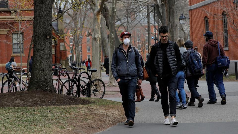 Deux jeunes hommes, dont un porte un masque, marchent dans une allée  de l'Université de Harvard.
