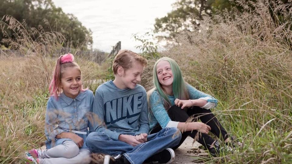 Trois enfants souriants assis dans l'herbe.