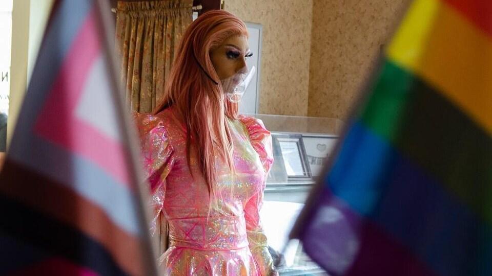 Une drag queen vêtue d'une robe rose est dans un restaurant entouré de drapeaux de la fierté.