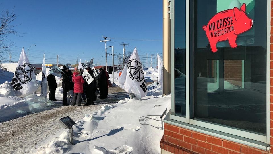 Une manifestation devant un édifice. Dans une fenêtre, un collant où il est indiqué «Ma Caisse en négociation».