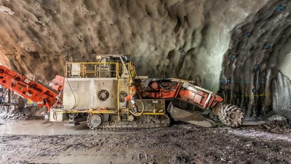 On voit l'excavatrice à l'oeuvre dans une cavité creusée dans le sol.