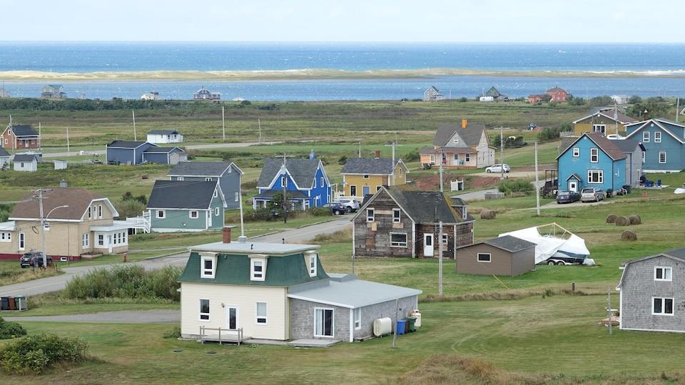 Des maisons colorées de l'île du Havre Aubert avec la mer en arrière-plan.