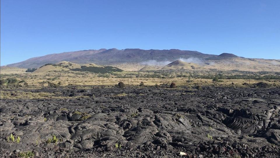 Des roches volcaniques en avant-plan, avec une montagne au loin